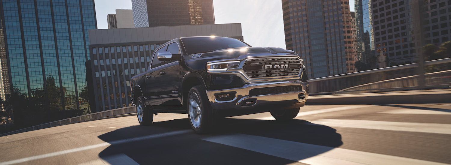A black 2019 Ram 1500 driving through a city street
