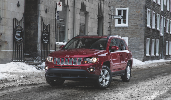 A Jeep Compass parked on a street on a snowy day in a city