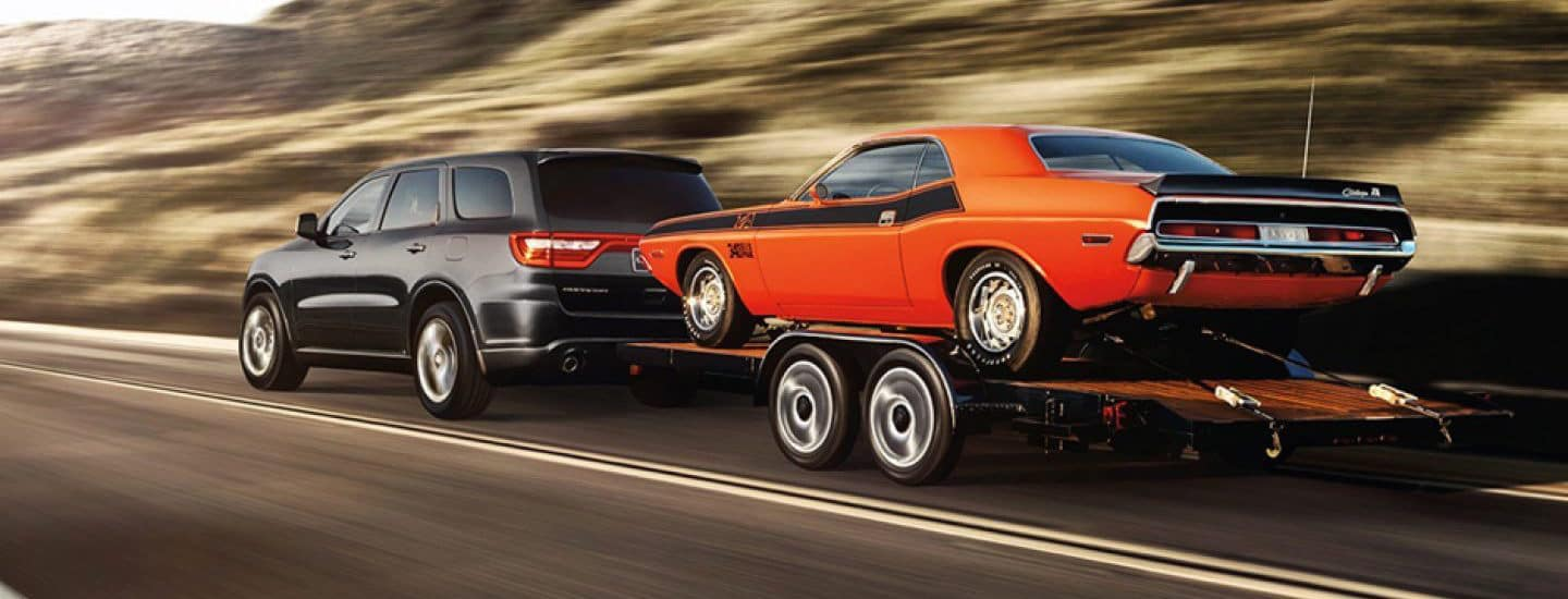 A Dodge Durango towing and orange muscle car