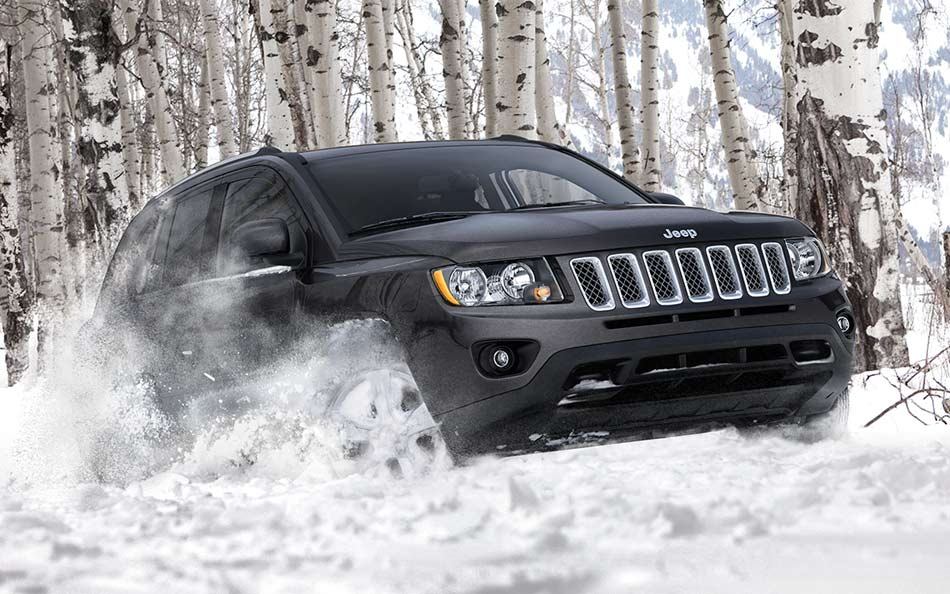 A black Jeep Compass driving through the snow