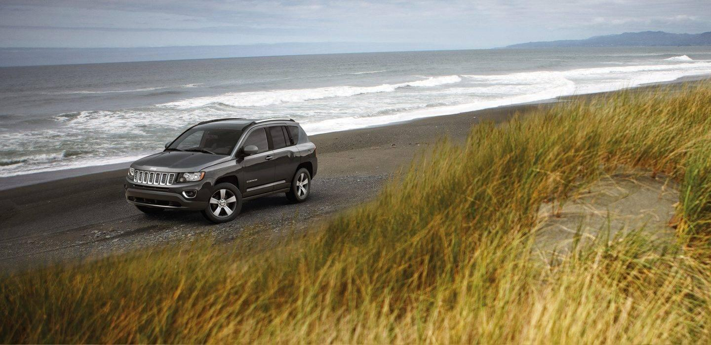 A Jeep Compass driving on the beach