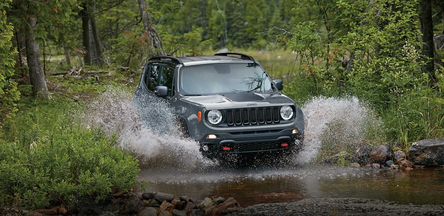 A Jeep Renegade driving through a river in the forest