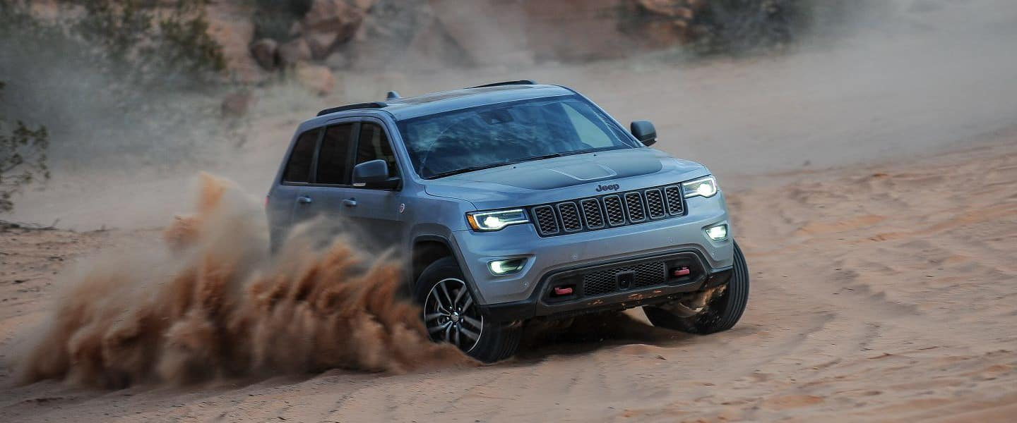 A silver Jeep Grand Cherokee offroading through the sand