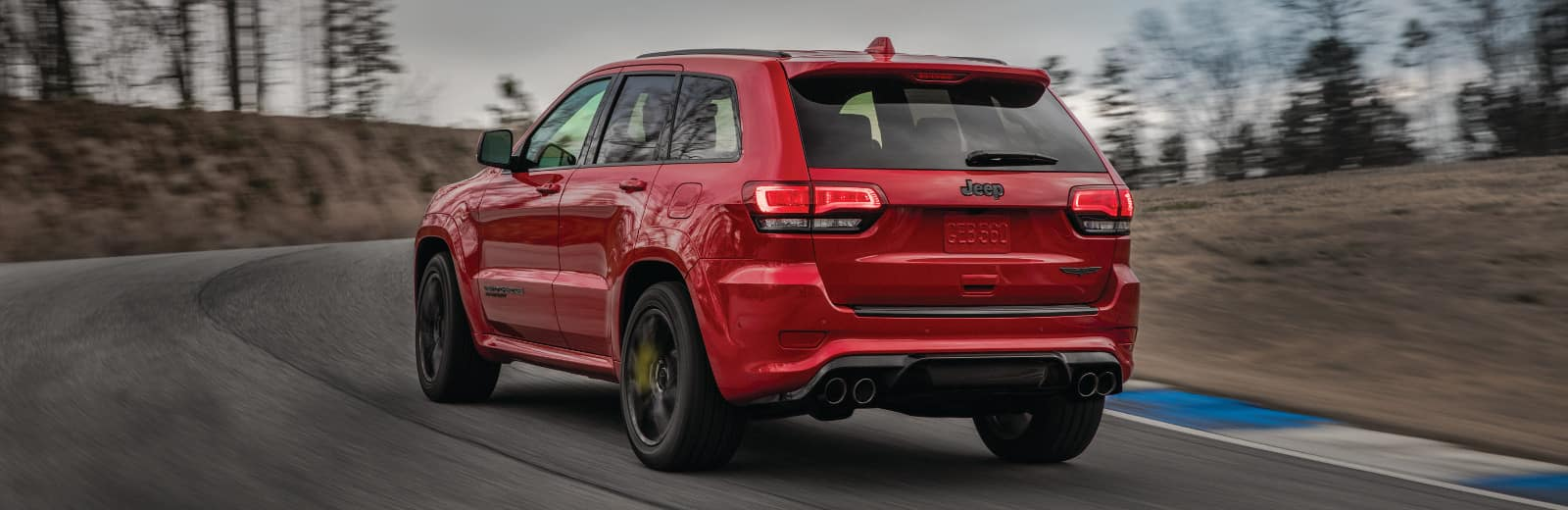 A 2018 Jeep Grand Cherokee driving down an open track