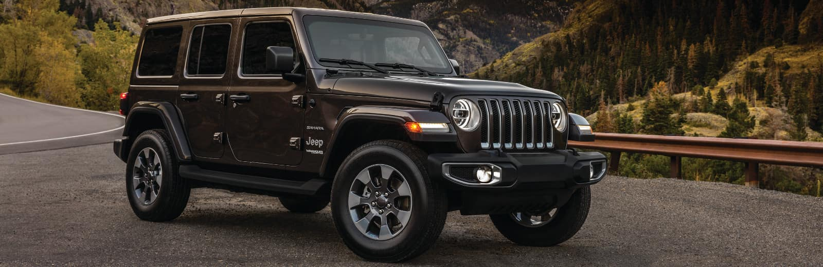 A Jeep Wrangler parked in front of the mountains