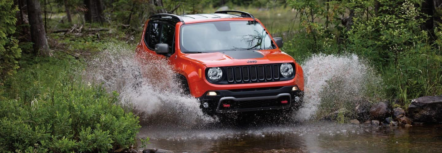 An orange Jeep Renegade driving through a river