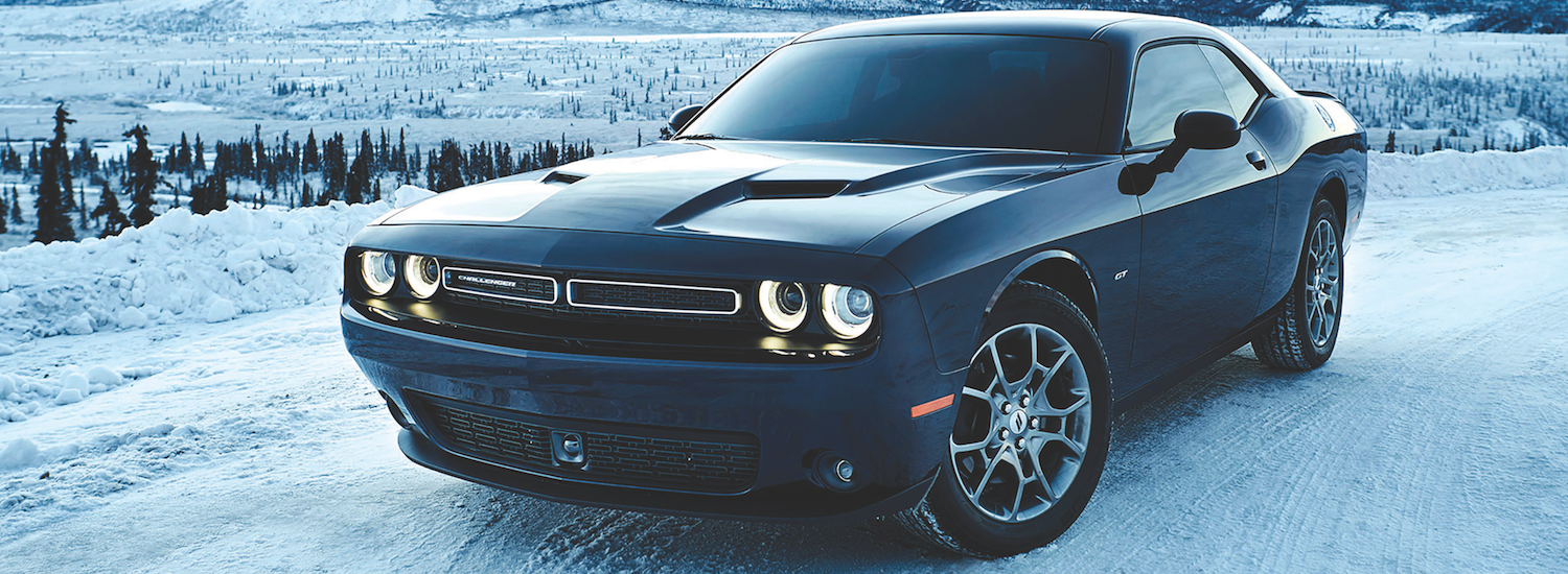 A black Dodge Challenger parked on a snowy hilltop in the winter