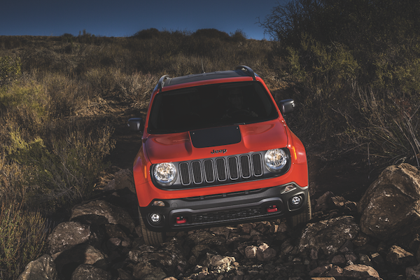 An Orange Jeep Renegade Offroading through a field and over rocks