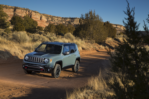 A grey Jeep Renegade driving on a dirt path through the desert