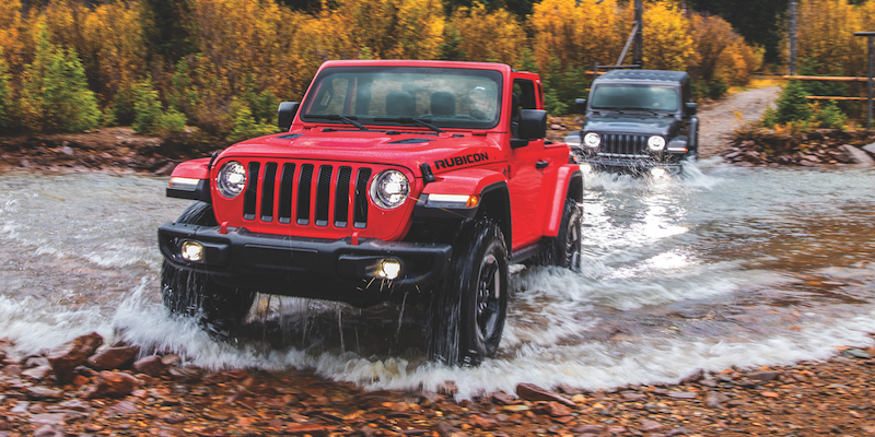 Red & Black Jeep Wranglers driving through a river while offroading through the forest