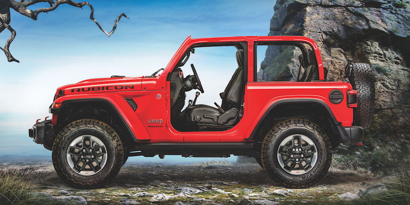 A red Jeep Wrangler with no doors parked on a mountain outlook