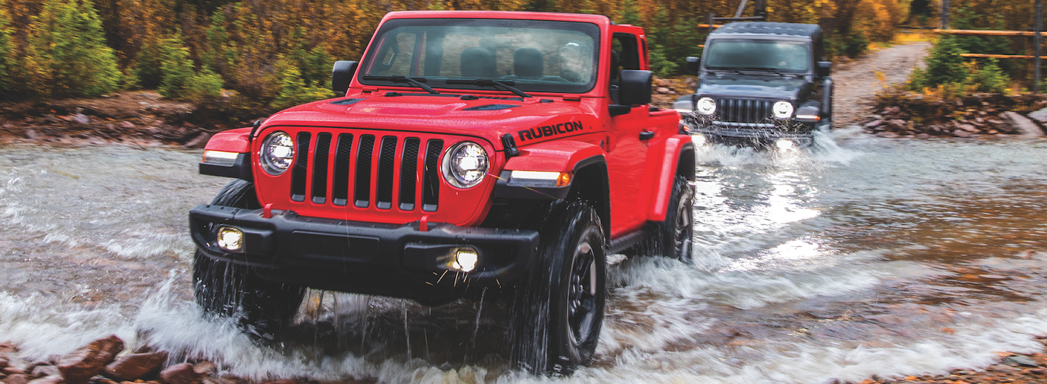 Two Jeep Wranglers offroading through a creek