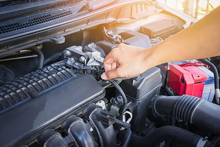 An auto service worker repairing an engine.