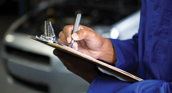 An auto service worker going through a checklist