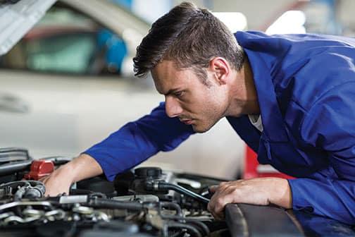A service worker looking under a car hood