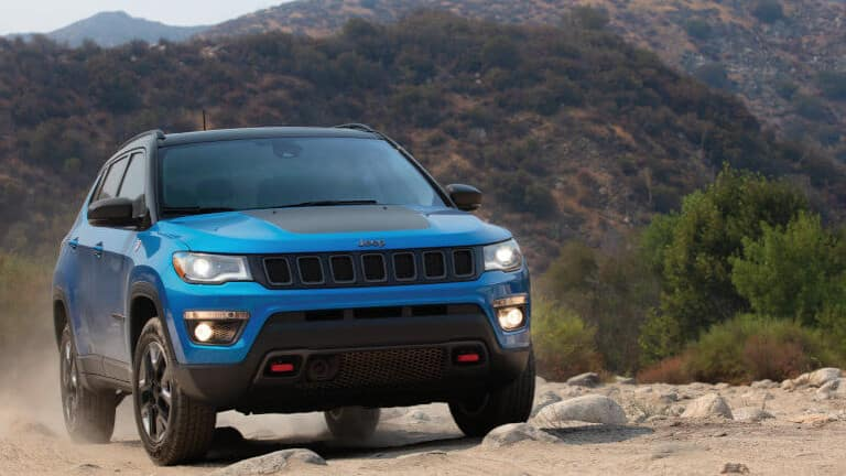 Blue Jeep Compass on dirt road