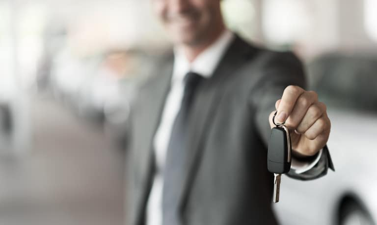 salesman handing car keys