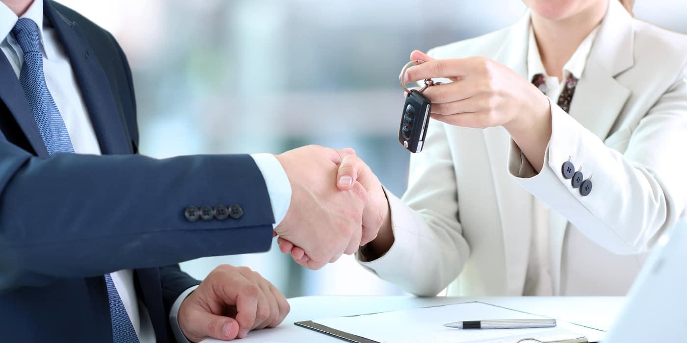 salesperson handling over car keys