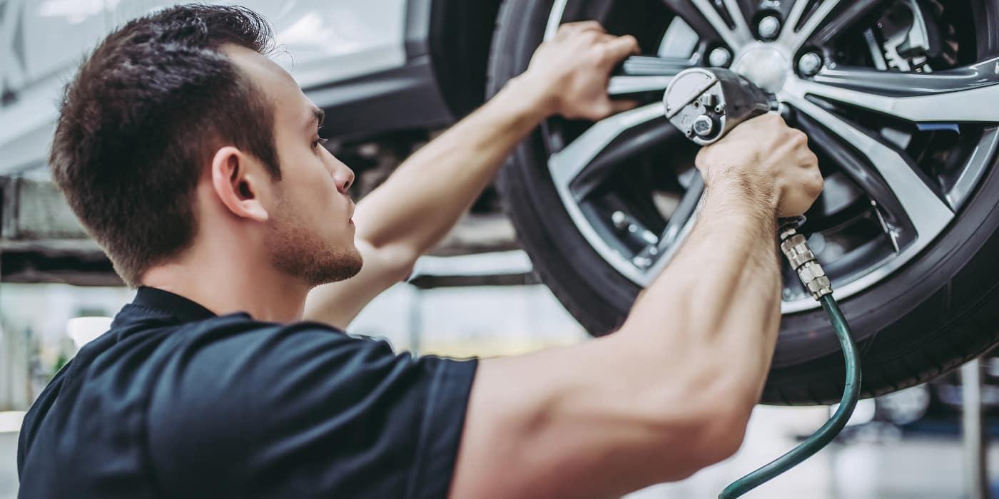 Mechanic fixing wheel on car