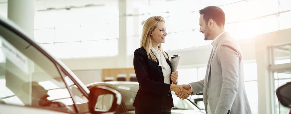 Salesperson selling cars at car dealership