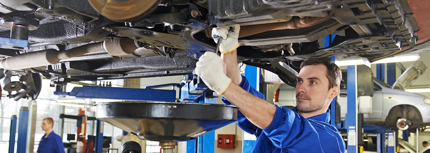 man working underneath car in auto body shop