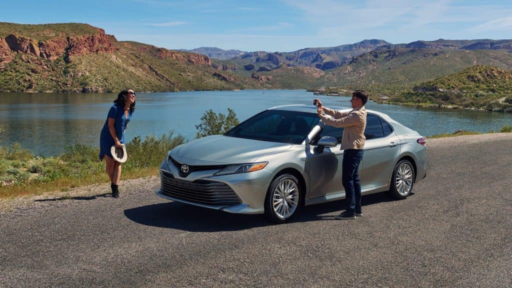 couple taking photos by 2020 camry
