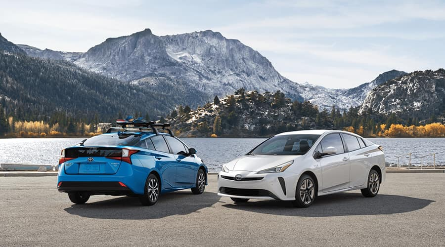 2 toyota prius cars parked near mountains