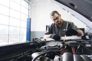 Man performing service on open hood of car
