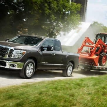 2018 Nissan Titan Towing Tractor on Dirt Road