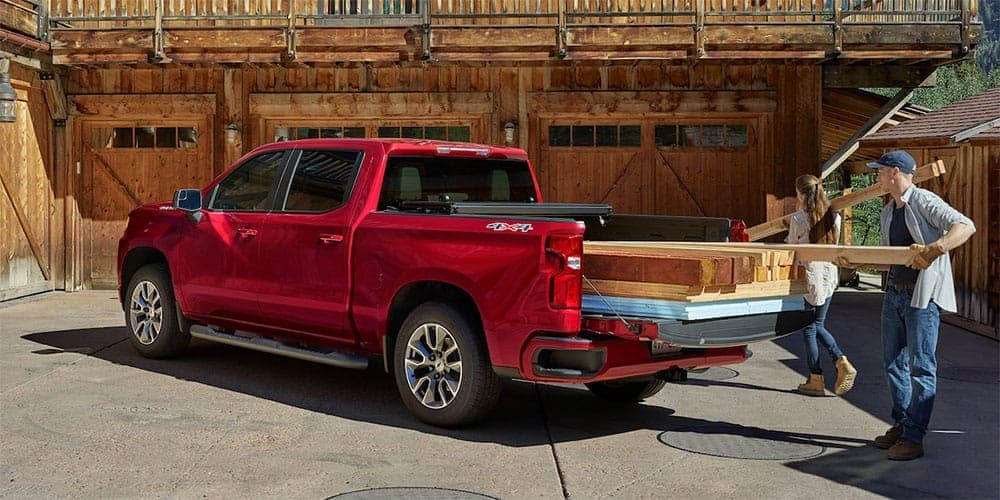 People loading wooden beams in 2019 Chevrolet Silverado bed
