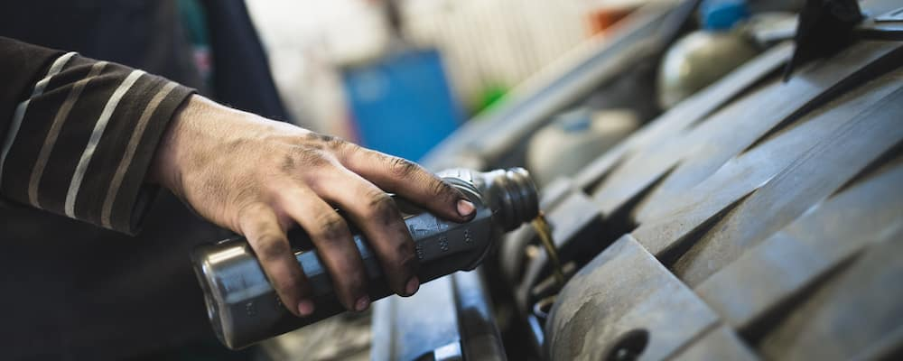 Unseen mechanic pouring new oil in car engine