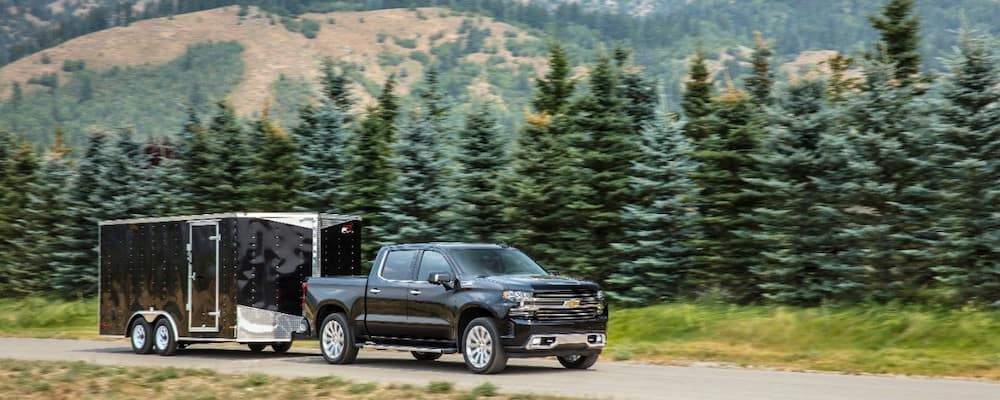 2019 Chevy Silverado towing trailer with forest and mountains in background