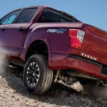Red 2019 Nissan Titan driving up hill from behind