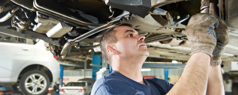 Auto mechanic working on car suspension under vehicle