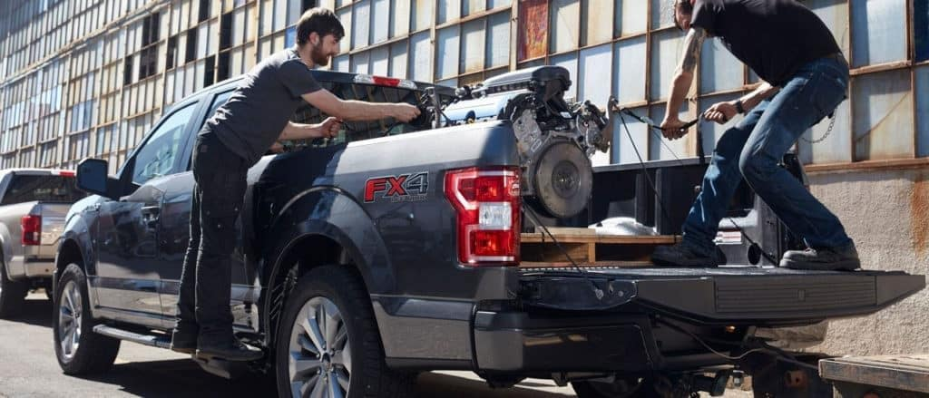 People loading engine into bed of 2018 Ford F-150