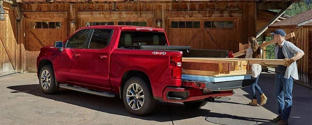 People taking wooden beams out of Red Chevy Silverado 1500