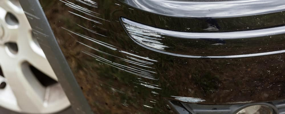 Close on bumper of black car with paint scratches
