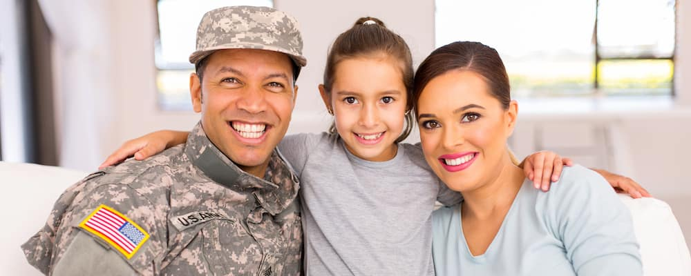 Smiling military family with man in uniform, daughter, and wife